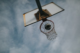 Basket ball entering into a basketball ring, at an urban court, with blue sky background. - 231853843