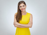 Smiling woman wearing yellow dress standing with arms crossed. - 231854095