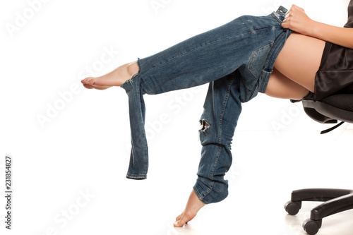 Leinwanddruck Bild Young woman trying to put on her tihgt jeans on white background