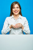 Smiling woman in white shirt holding water glass with blak card,