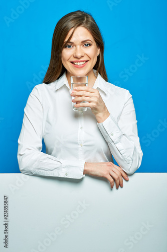 Uśmiechnięta biznesowa kobieta trzyma wodnego szkło na błękita plecy.