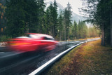 Blurred red car in motion on the road in autumn forest in rain. Perfect asphalt mountain road in overcast rainy day. Roadway, pine trees in italian alps. Transportation. Highway in foggy woodland - 231859631
