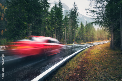 Leinwanddruck Bild Blurred red car in motion on the road in autumn forest in rain. Perfect asphalt mountain road in overcast rainy day. Roadway, pine trees in italian alps. Transportation. Highway in foggy woodland