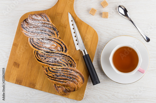 Poster Bun with poppy, knife on cutting board, sugar cubes, tea