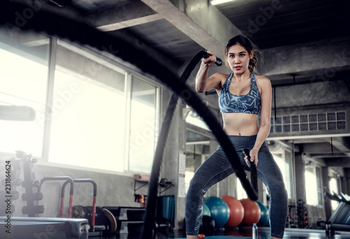 Wall mural Asian sportswoman fit training with battle rope in fitness gym. Sport and workout motivation concept.