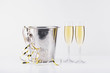close up view of bucket, festive garlands and glasses of champagne on grey backdrop
