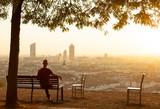 Man on a bench enjoying the summer sunrise over a city. Lyon, France. - 231870298