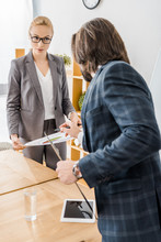 """Постер, картина, фотообои """"young woman and man standing at meeting in office"""""""