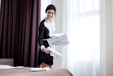 Clean room. Positive hotel maid leaving towels on the bed while finishing cleaning the room - 231872407