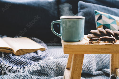 Cup of hot drink on wooden table. Living room interior with blue sofa on background. Cozy winter or autumn concept - 231872658