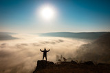 Black silhouette of a man standing on a rock over a foggy valley - 231873428