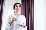Positive emotions. Delighted smart businesswoman being in a great mood while drinking her coffee - 231876200