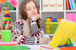 Leinwanddruck Bild - Portrait of a cute little girl doing homework