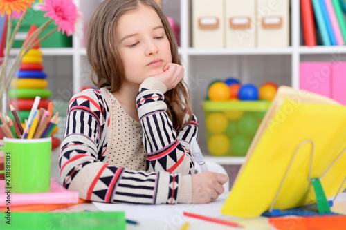 Leinwanddruck Bild Portrait of a cute little girl doing homework