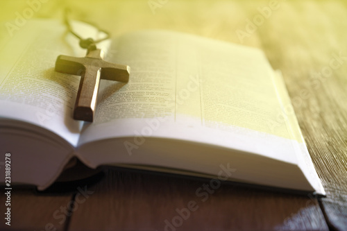 Open holy bible and wooden cross