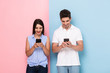 Leinwanddruck Bild - Image of european man and woman wearing earphones and using smartphones, isolated over colorful background