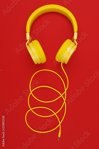 Yellow headphones on red background. Music concept. - 231892438