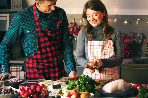 Leinwandbild Motiv Couple celebrating Christmas in the kitchen cooking christmas duck or Goose