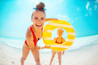 happy mother and child with yellow inflatable lifebuoy on beach