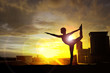 Silhouette of woman practicing yoga on the building at sunset