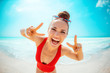 happy young woman in red swimwear on beach showing victory