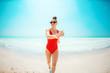happy modern woman in red beachwear on beach having fun time