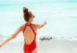 smiling young woman in red beachwear on beach having fun time