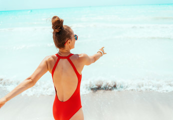 smiling young woman in red beachwear on beach having fun time