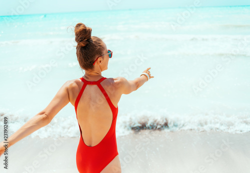 smiling young woman in red beachwear on beach having fun time © Alliance