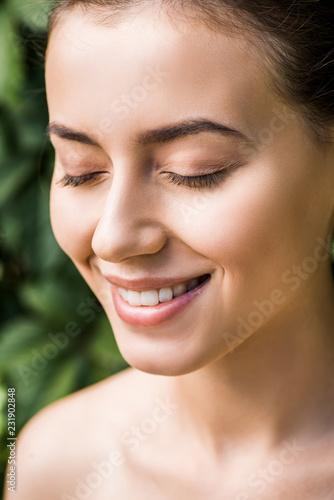 uśmiechnięta młoda kobieta z zamkniętymi oczami na zielonym tle