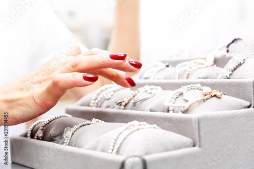 Biżuteria i dodatki. Kobieta ogląda biżuterię w salonie jubilerskim © Robert Przybysz