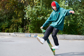 Full length portrait of young man doing skateboard stunts in extreme sports park, copy space