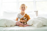 A Cheerful little girl in bed having fun - 231907094