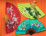chinese fan on orange wooden background
