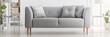 Light grey sofa with cushions in real photo of white living room interior with silver end tables and glass lamps