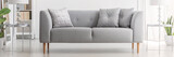 Light grey sofa with cushions in real photo of white living room interior with silver end tables and glass lamps - 231908644