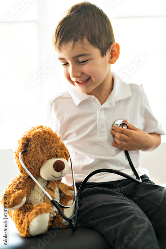 A doctor boy playing and cure bear at the pediatric © pololia
