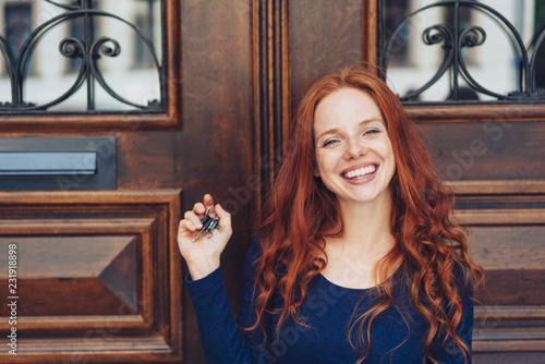 Leinwanddruck Bild Grinning woman holding keys in closed hand