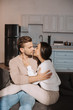 romantic young couple kissing on couch at home