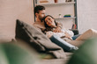 attractive young couple cuddling on couch at home