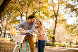 Active senior couple together enjoying romantic walk with bicycle in golden autumn park - 231924603