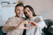 beautiful young couple making heart symbol with hands and looking at camera