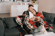 Leinwanddruck Bild - beautiful young couple with glasses of white wine relaxing on couch under plaid