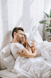 beautiful young couple embracing in bed in morning
