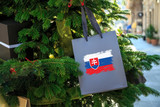 Slovakia flag printed on a Christmas shopping bag. Close up of a shopping bag as a decoration on a Xmas tree on a street. New Year or Christmas shopping, local market sale and deals concept.