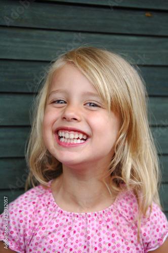Leinwanddruck Bild Kleines Mädchen lächelt glücklich.