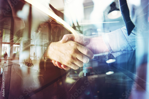 Handshaking business person in the office. concept of teamwork and partnership. double exposure