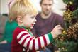 Cute kid decorating Christmas tree