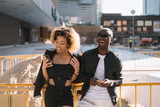 Afro couple using the smartphone on the street - 231948678