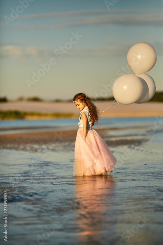 The girl runs along the beach with balloons in their hands.